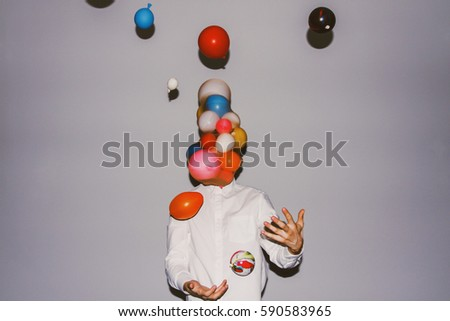 Artistic creative photography. Man wearing white shirt, throwing balloons up high.
