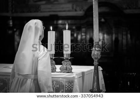 Artistic dark black and white edit of a catholic nun blowing the altar candles in a church