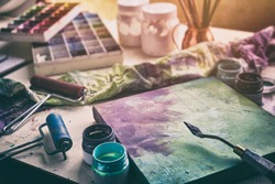 Artistic equipment - canvas and palette knife, paint brushes, multicolored paints in artist studio.