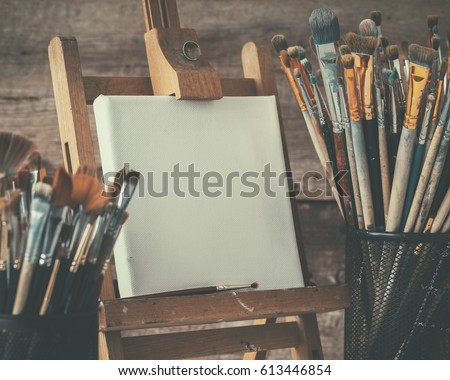 Artistic equipment: empty artist canvas on easel and paint brushes in a artist studio. Retro toned photo. #613446854