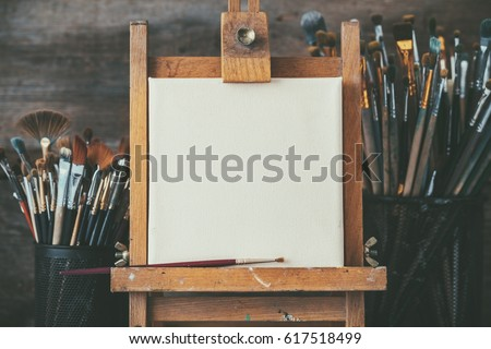 Artistic equipment in a artist studio: empty artist canvas on wooden easel and paint brushes Retro toned photo. #617518499