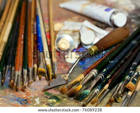Artistic equipment: paint, brushes, spatula and art palette. Shallow depth of field