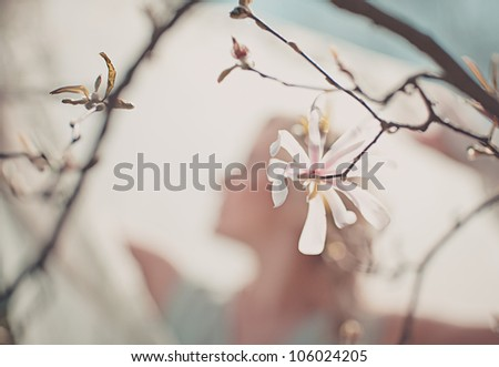 Artistic ethereal blurred portrait of a woman with focus to a delicate magnolia blossom on a twig in the foreground