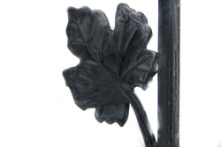 Artistic forging. Part of the forged fence. Leaves from metal.