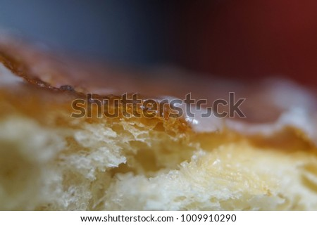 Artistic high resolution extreme close up of sugar coated crust of polish donut with blurred blue background and red accent. Creative shot of homemade dessert. #1009910290