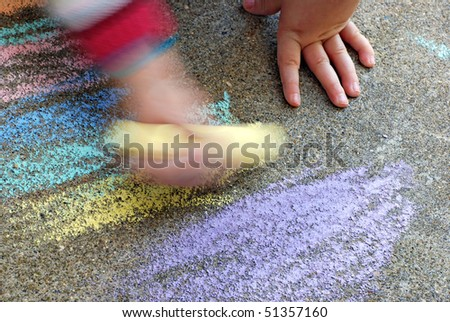 Artistic image of young child scribbling aggressively with colorful sidewalk chalk.  Motion blur created in camera for effect.