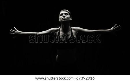 Artistic in studio, low key photo of slim attractive female in workout attire