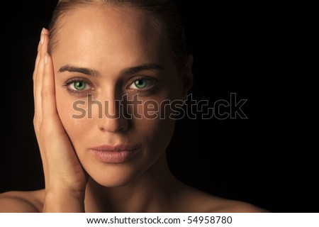Artistic low key head shot of a woman with vivid green eyes