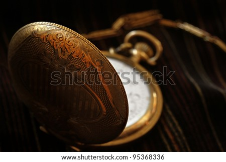 Artistic low key image of antique pocket watch on striped velvet fabric.  Macro with extremely shallow dof.