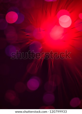 artistic macro of a fiber optics light wand with round shaped colorful light spots, merging into one bright red spot