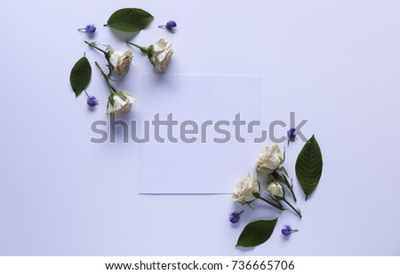 Artistic mockup for your artwork with beautiful flowers and leaves and empty card shot from the top. Flat lay minimalistic composition. #736665706