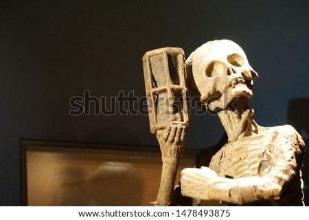 Artistic model of skeleton holding hour glass in right hand Black backdrop of negative space contrasts with metaphor of death