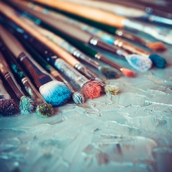 Artistic paintbrushes on artist canvas covered with oil paints