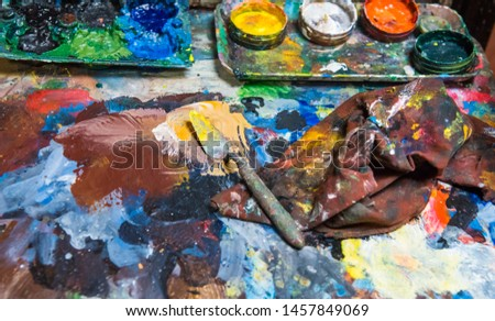 Artistic paintbrushes, paints and palette knifes on an old wooden palette #1457849069