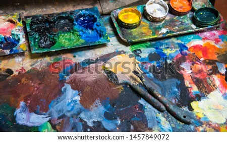 Artistic paintbrushes, paints and palette knifes on an old wooden palette #1457849072