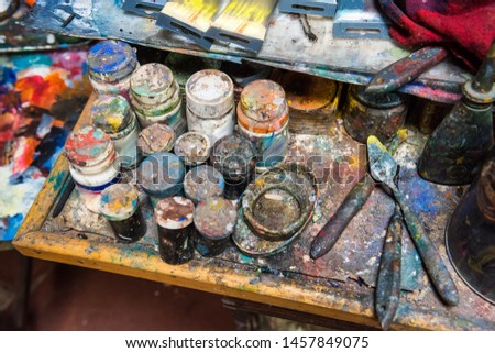 Artistic paintbrushes, paints and palette knifes on an old wooden palette #1457849075