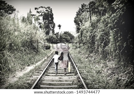 artistic photograph of a mother and her son walking between the train tracks with a livelihood of misery with faded color effects to give it that dramatic moment feeling,