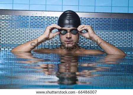 Artistic portrait of swimmer resting on swimming pool - stock photo