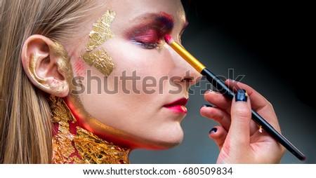 Artistic professional make up applies eye shadow. Beautiful woman face.