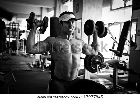 artistic shot, black and white, of a young bodybuilder hard training in the gym: dumbbell shoulder press