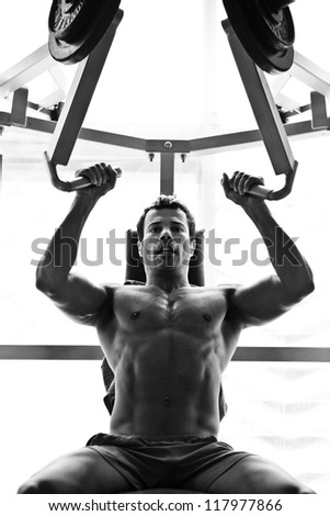 artistic shot, black and white, of a young bodybuilder hard training in the gym: shoulder press