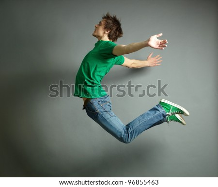 Artistic shot of a guy jumping high and posing meanwhile