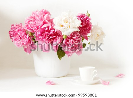 Artistic still life with peonies and cup of coffee and petals