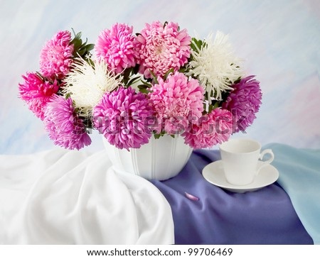 Artistic still life with summer flowers and cup on painting background