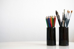 Artistic tools - colored pencils and watercolor brushes arranged in two ceramic cups on white table, white wall background