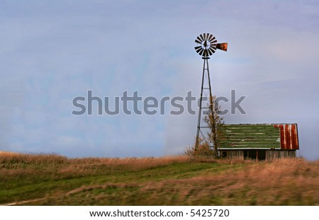 Artistic view of old barn and windmill with wind blown field