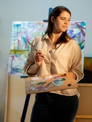 Artistic woman. Painting process. Creating artwork. Fine art school. Inspiration muse. Smiling thoughtful lady holding palette with mixed colors paints and knife in light interior studio.