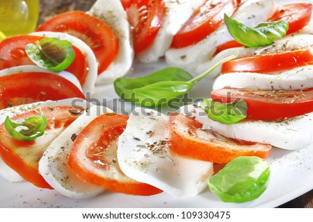 Artistically arranged cheese and tomato salad in alternating slices of red and white garnished with fresh herbs