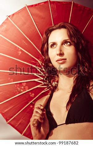 Artistically toned image of a serene woman in bikini sheltering under a red parasol from the heat of the sun on an idyllic peaceful retreat in china
