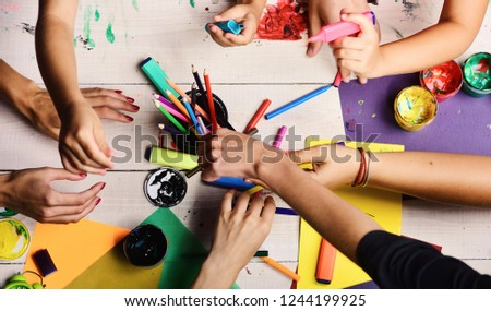 Artists hands with stationery and colored paper. Hands hold markers, pencils and paints, top view. Art supplies in male and female hands on white desk background. Creativity and art concept #1244199925