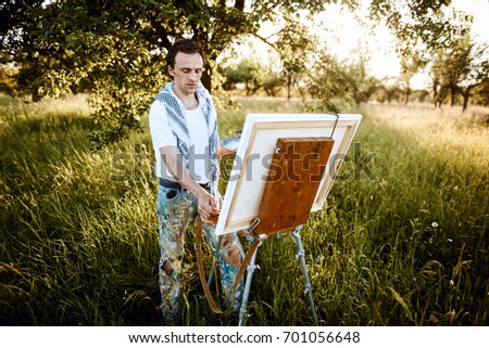 Artists Sketching in the garden. Male artist on painting on canvas in outdoor. Fine art artist. Male artist working on painting #701056648