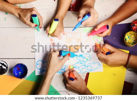 Artists wooden table with paints and colored paper. Hands hold colorful markers and draw kids illustration, top view. Art and idea concept. Markers in male and female hands draw on white paper #1235369737
