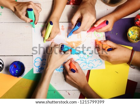 Artists wooden table with paints and colored paper. Markers in male and female hands draw on white paper. Art and artwork concept. Hands hold colorful markers and draw kids illustration, top view #1215799399