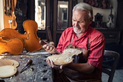 Arts and crafts. Senior carpenter craftsman carving wood in his old-fashion workshop. An experienced caucasian elderly man manually making masterpiece. Handcraft and creativity.
