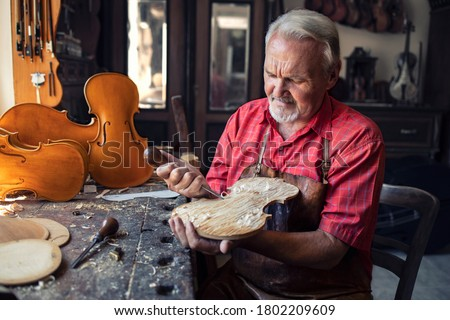 Arts and crafts. Senior carpenter craftsman carving wood in his old-fashion workshop. An experienced caucasian elderly man manually making masterpiece. Handcraft and creativity. Stock photo ©