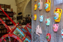 Arts and crafts, souvenir shop and workshop in Ragusa, Sicily. Traditional ceramic products displayed on a wooden wall, typical vases and sicilian cart
