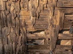Artsy background of a deteriorating wooden shingled wall with bare nails and fabric scraps.