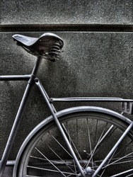 Artsy photo of a bicycle standing against a wall in black and white