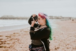 Artsy woman taking a photo at a beach