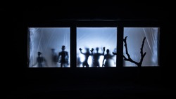 Artwork decoration. Old house with a big windows and zombies inside. Blurred scary silhouettes at window. Horror Halloween concept