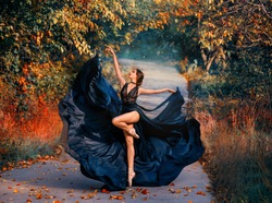 Artwork in bright colors. Beautiful girl ballerina dancing on the road. Autumn nature background. Fashion model posing creatively in motion. A long black dress flies in the wind. Fantasy woman dancer