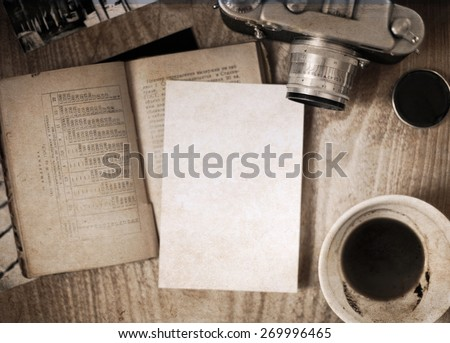 Artwork in retro style, old-fashioned camera, opened book, empty cup of coffee