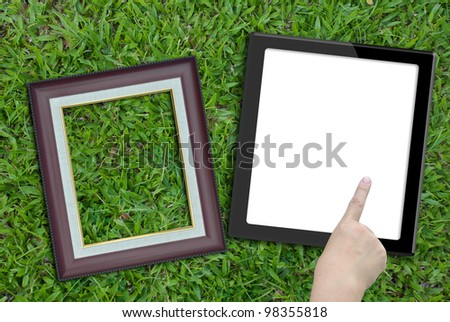 Artwork of tablet computer with hand and photo frame on nature background.