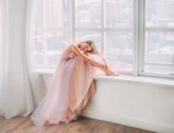 Artwork sleeping dream beauty. Blonde young woman with long flowing hair. sits on windowsill hugs legs. vintage room white window. Princess cute face Girl. luxury pastel beige purple graduation dress
