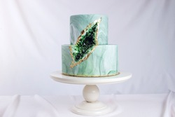 Artwork. Wedding cake decorated like a stone marble with emeralds in a cut on a background of wavy fabric. food design. trends