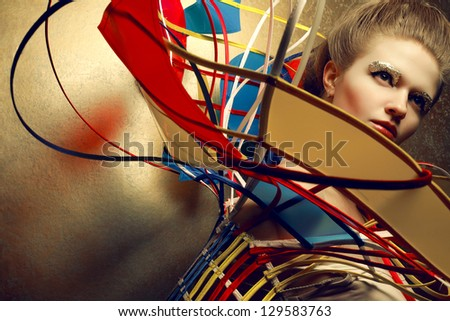Arty portrait of a fashionable blonde with a perfect golden makeup in a cape done in avant-garde (a-la constructivism and suprematism) style. Close up. Studio shot
